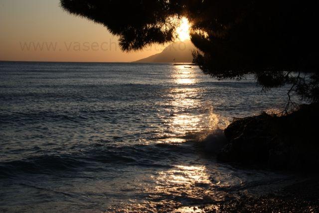 Západ slnka Chorvátsko - Slnko zapadá nad Jadranským morom v Chorvátsku na dovolenke na Makarskej riviére v mestečku Brela. V strede je vidieť modrú vlajku (Blue Flag) ocenenie, ktoré získala najkrajšia pláž v Brele Punta Rata. Chcem dovolenku a rezervovať na leto ubytovanie v Chorvátsku