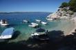 Člny v malej zátoke - Malá zátoka a pláž v mestečku Brela, skalný výbežok do mora, pekné miesto na potápanie. Predaj ovocia z člna, veľmi častý spôsob predaja v prímorských mestách cez dovolenku.